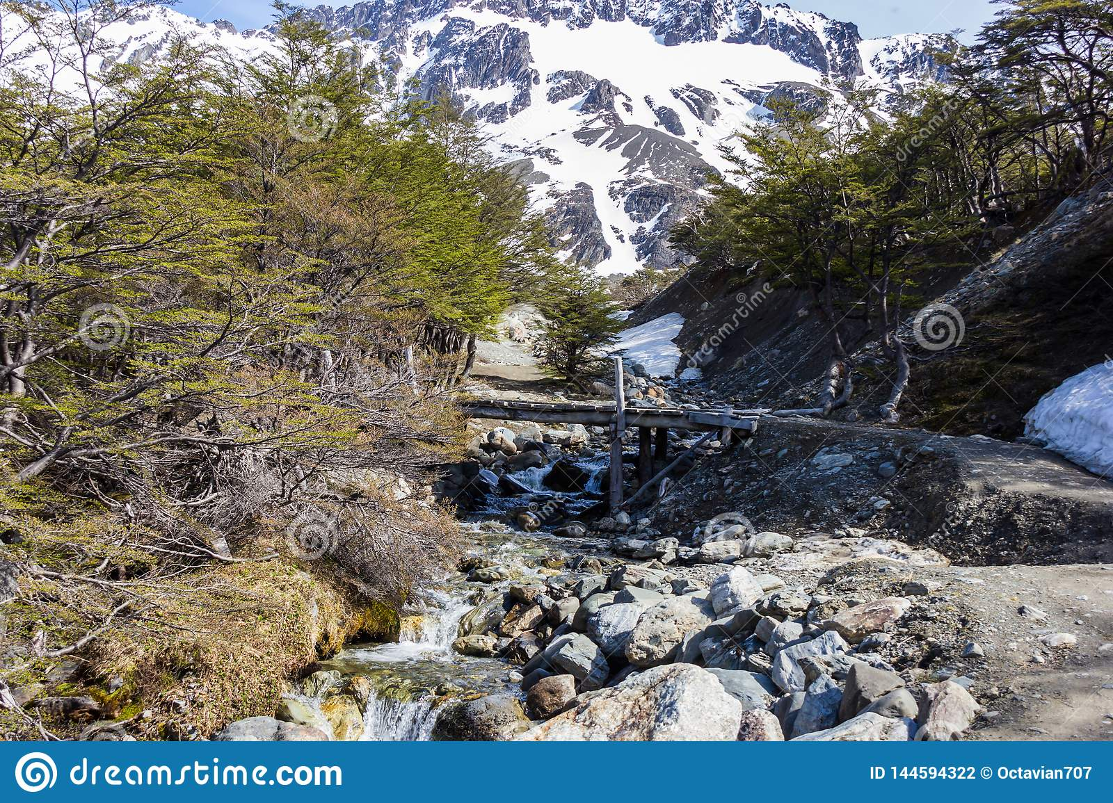 Wooden bridge over small river in the mountains