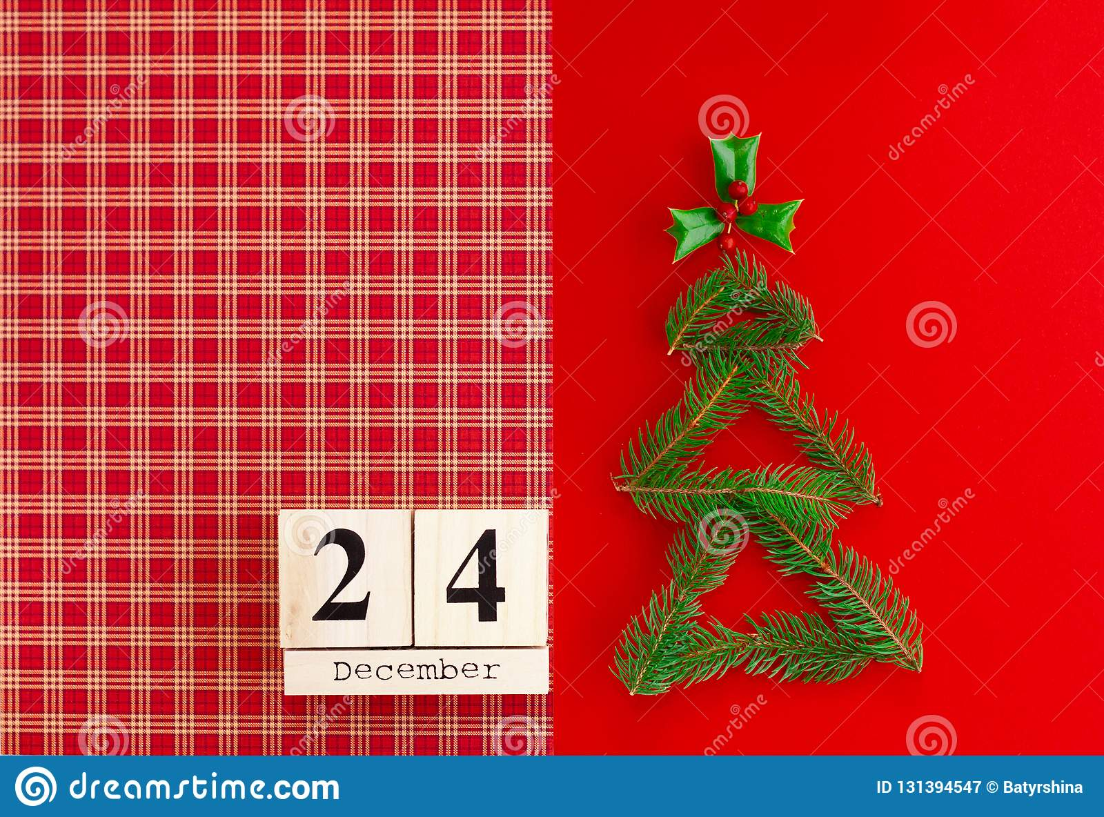 wooden calendar with 24 december date on the red background new year and christmas concept