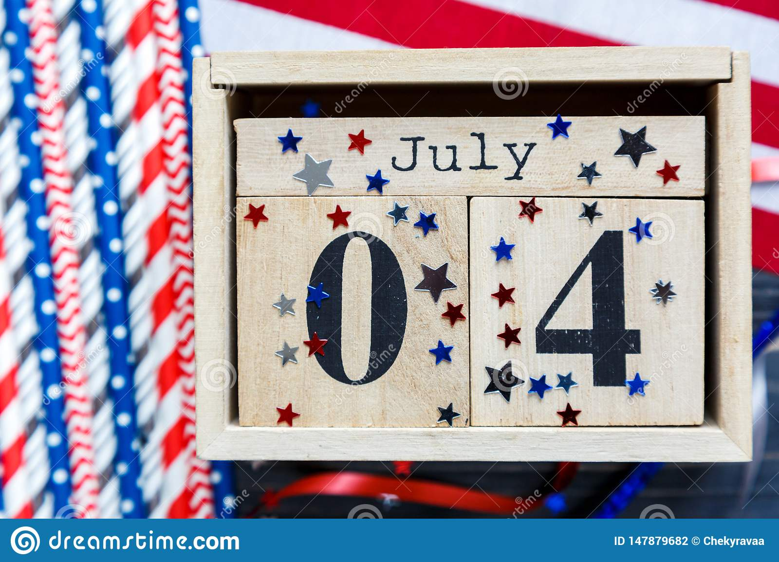 Wooden calendar 4th of July day of American independence, decorations, flag, candles, straws. USA holiday decorations