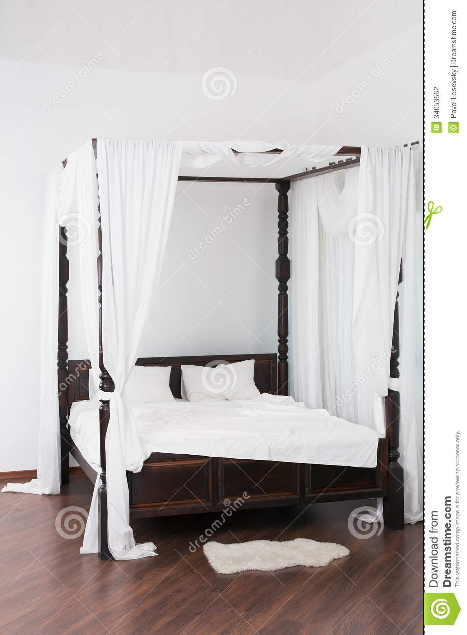 Wooden Canopy Bed And A White Hide On The Floor Stock