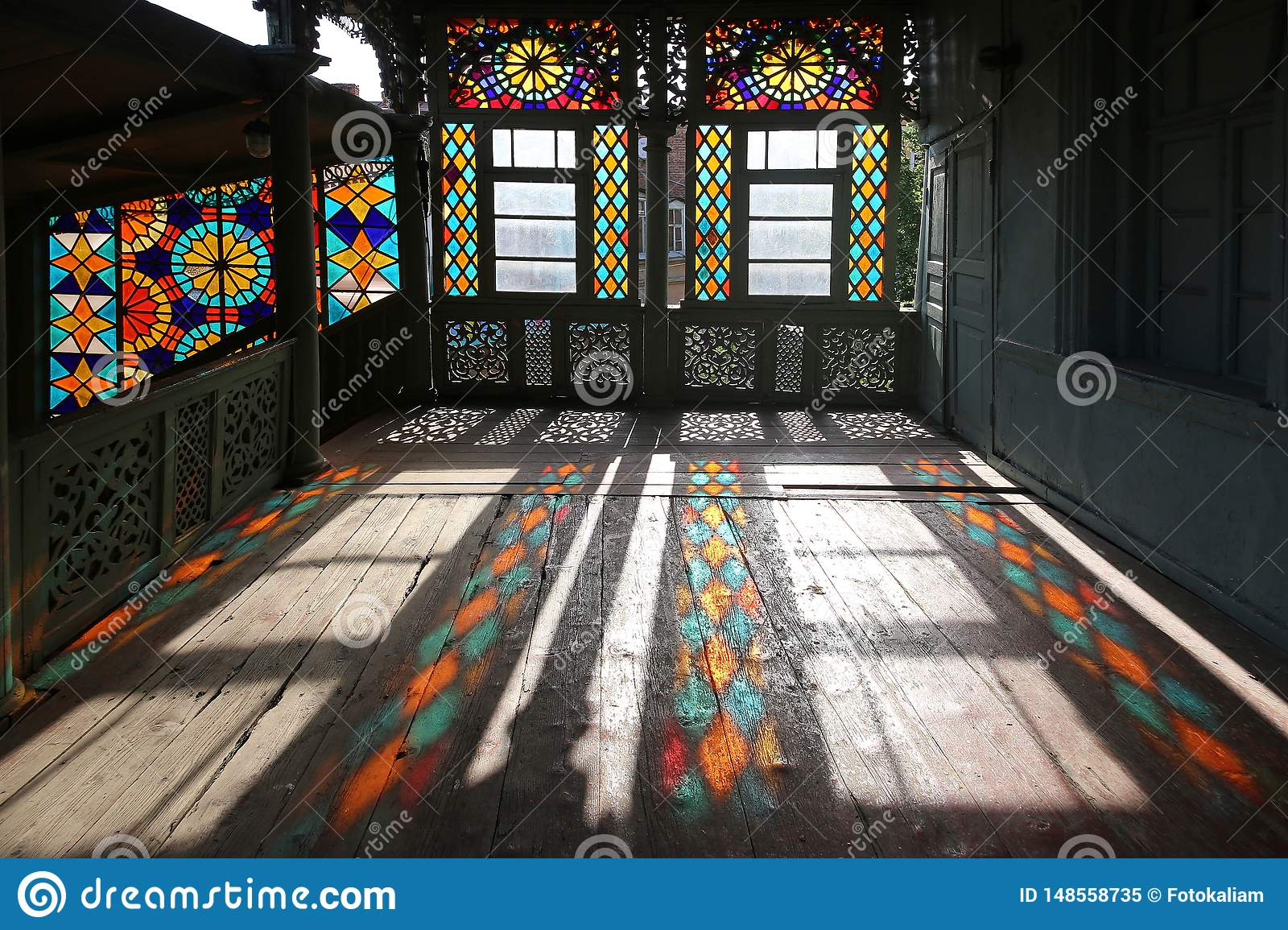 Wooden carved balcony in traditional Georgian style with stained-glass windows