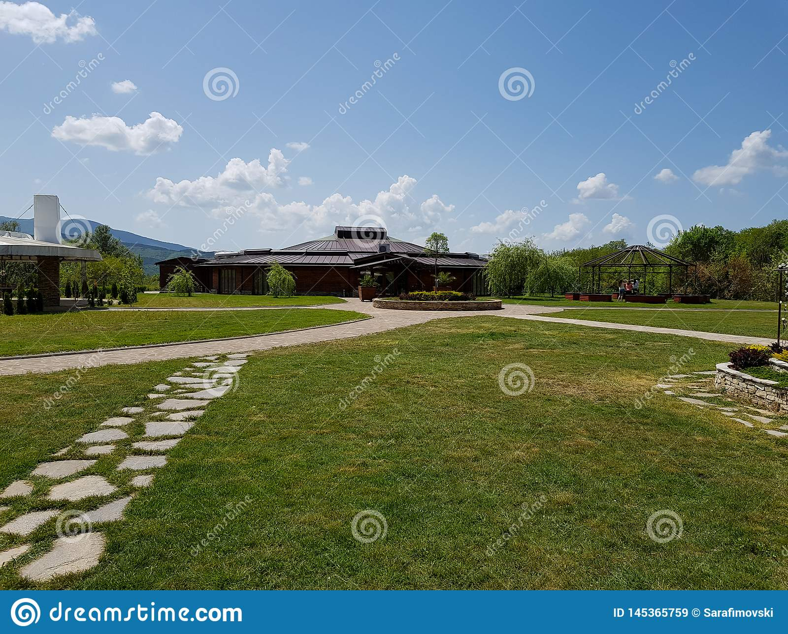 Wooden ceremony, wedding restaurant with grass and roads made of stones.
