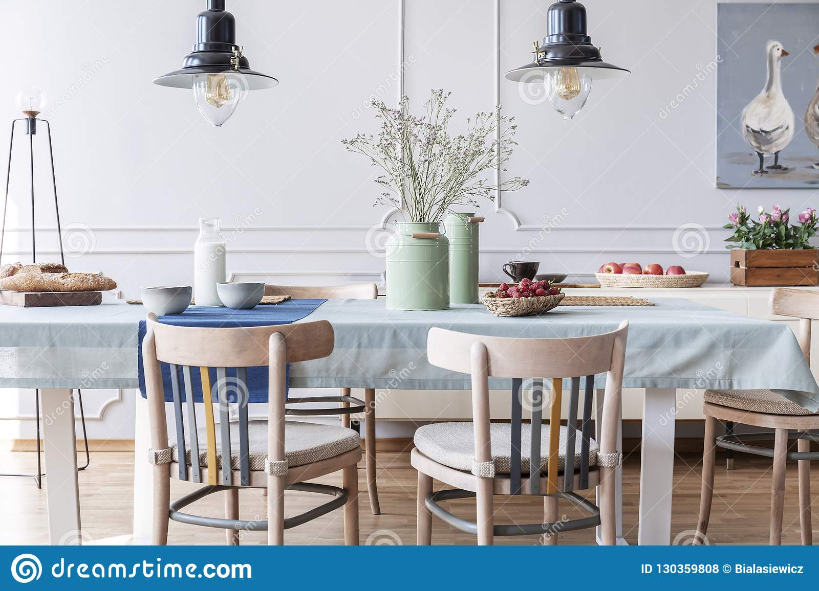 Wooden chairs at table with flowers and food in white cottage dining room interior with lamps and poster. Real photo