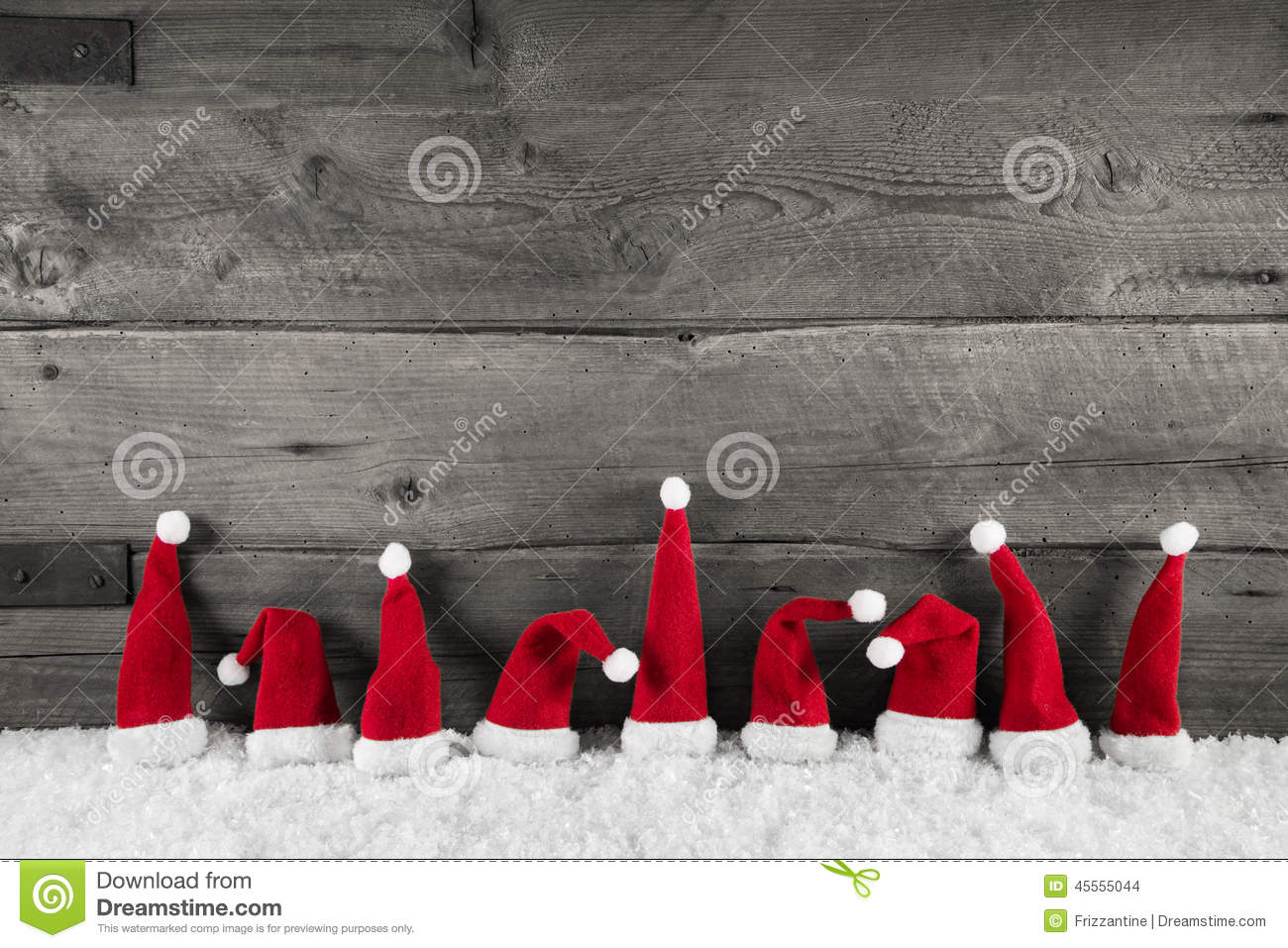 Wooden christmas background with red santa hats for a festive fr
