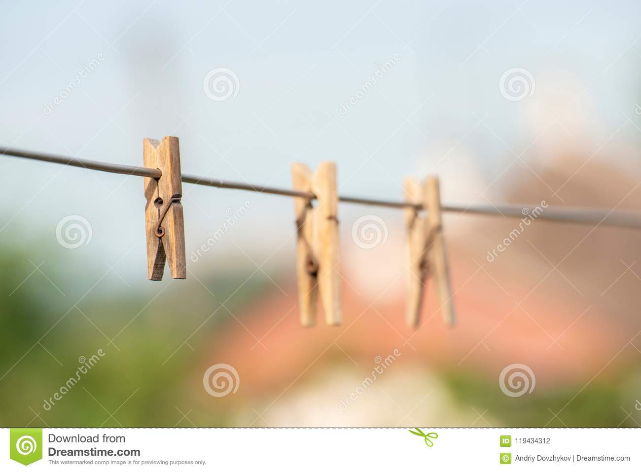 Wooden Clothespins Hanging On A Steel Wire On A Dark Background