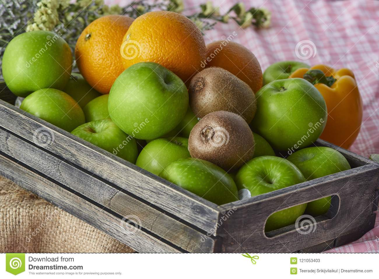 Oranges,kiwis and apples in a wooden crate