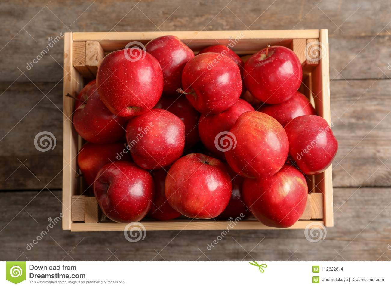 Wooden crate with fresh red apples on table