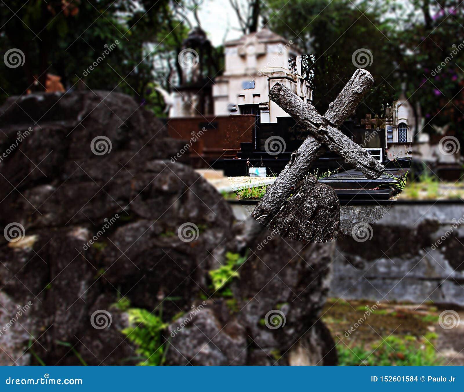 Wooden cross leaning on rock.
