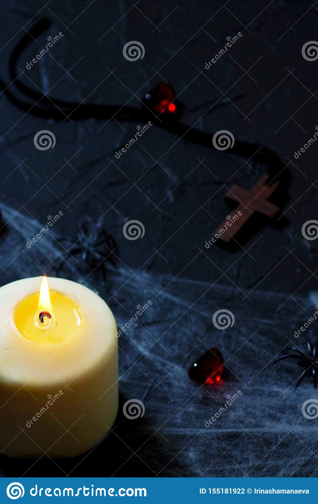 Halloween wooden cross lying next to a burning candle on a web with spiders and bats on a black background. vertical
