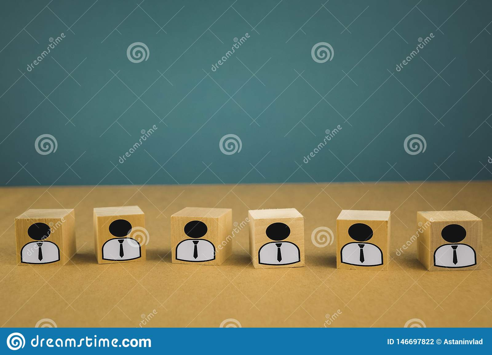 wooden cubes standing in a row, meaning wage workers standing in one line, abstraction on a blue background