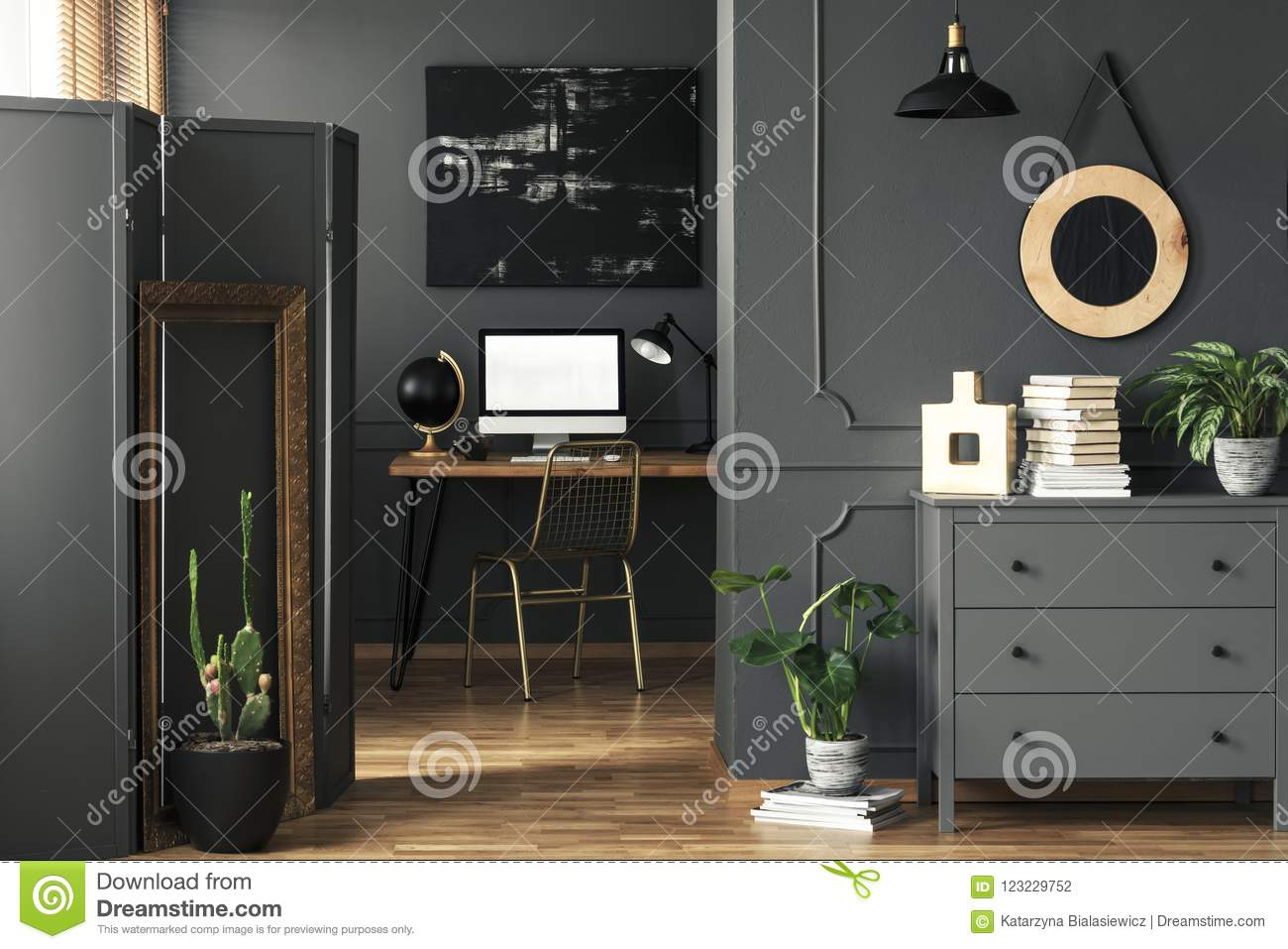 Wooden cupboard with decor, fresh plant and books standing in the real photo of open space living room interior with wainscoting