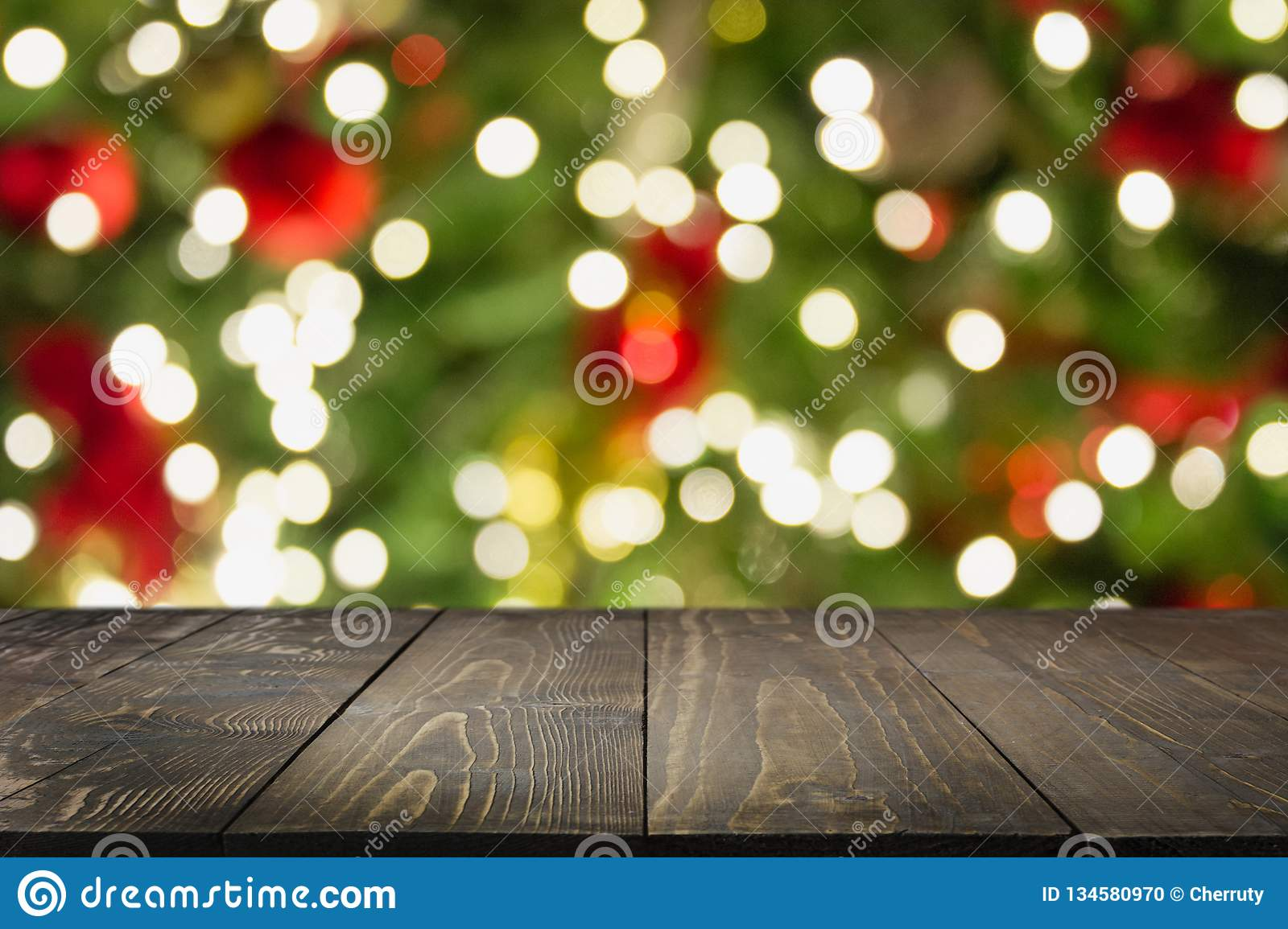 Christmas Tree Display Board.Wooden Dark Tabletop And Blurred Christmas Tree Bokeh Xmas