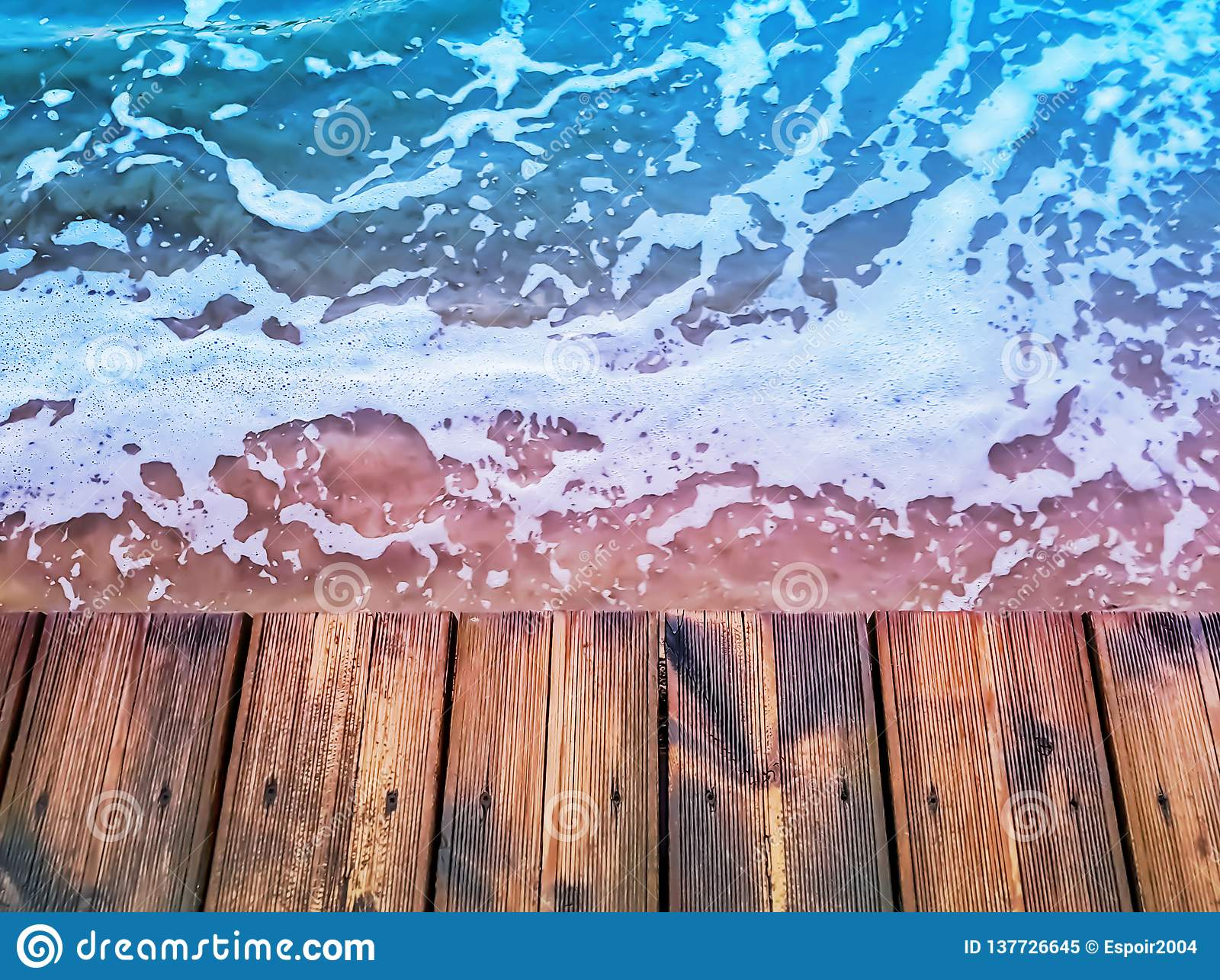 Wooden deck waterfront floor background texture and blue sea water surface with foam
