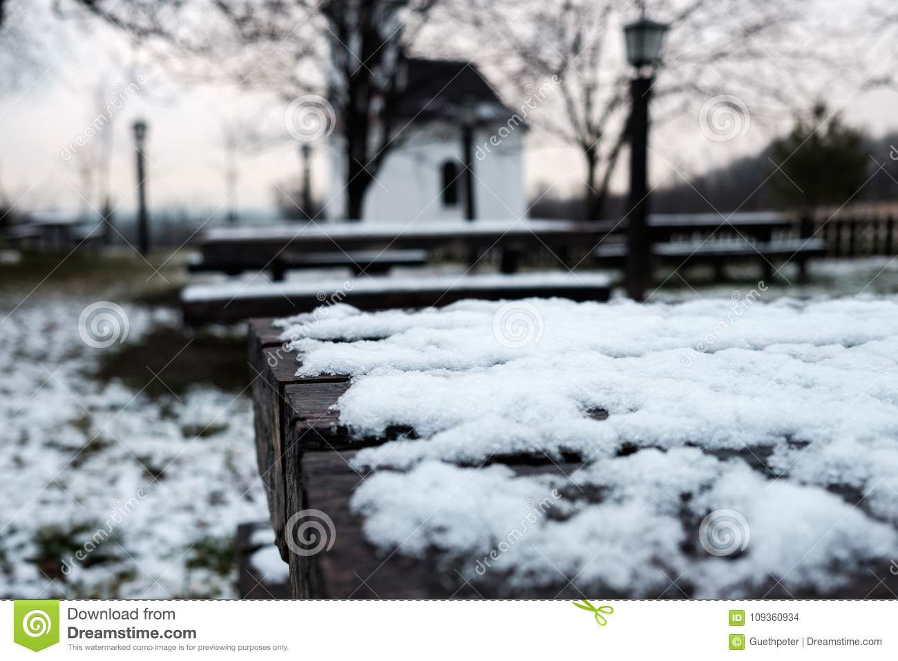 Wooden Desk In Garden Covered By Snow Lamps And Small Church In