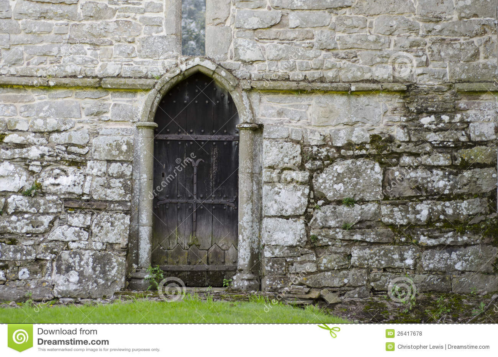Wooden door in 14th century stone church wall stock photo for Door of stone