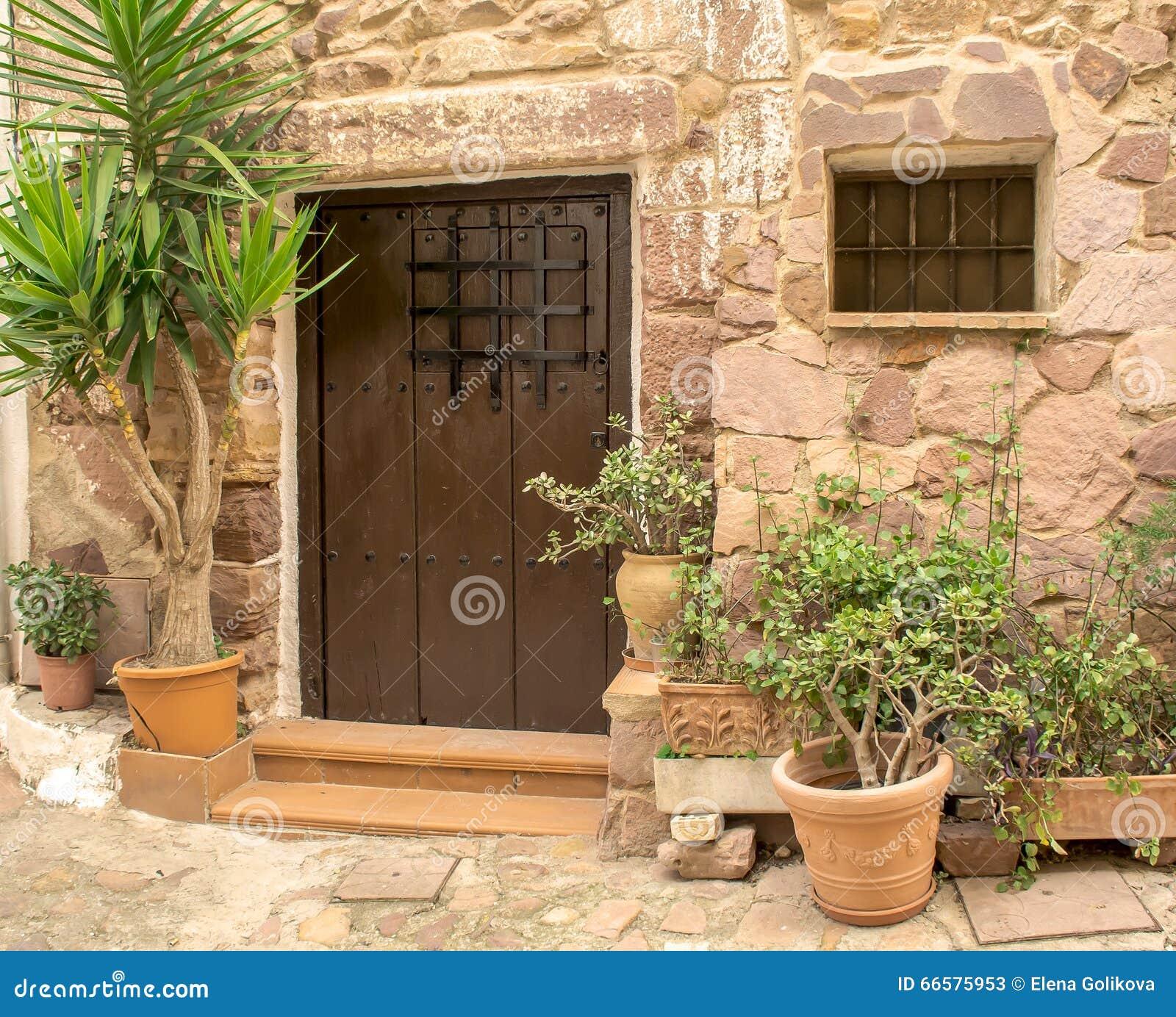 Wooden front door of old stone brick house royalty free for Door in spanish