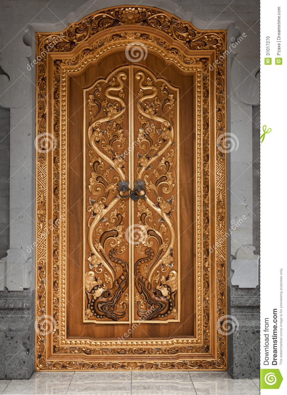 wooden door of an old temple with carvings indonesia