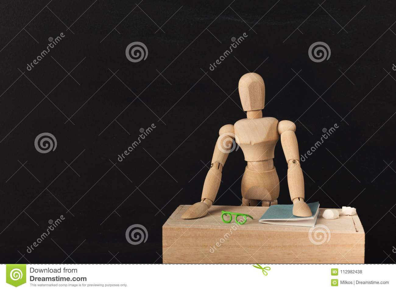 Wooden figure at workplace against black background