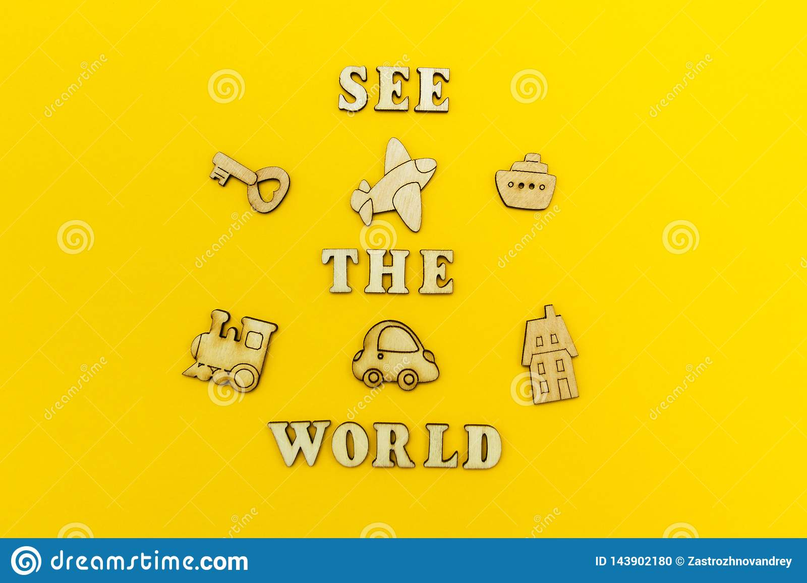 Wooden figures of an airplane, a train, a ship, a car. The inscription `see the world` on a yellow background.