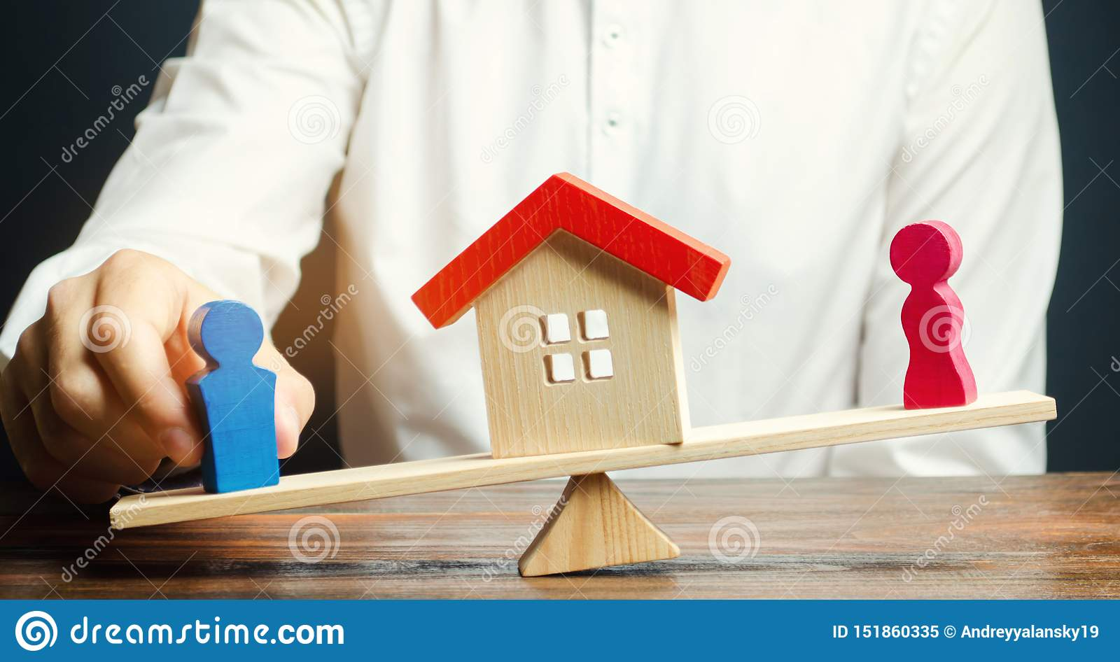 Wooden figures of a man and a woman on scales and a house between them. Division of property by legal means. Clarification of