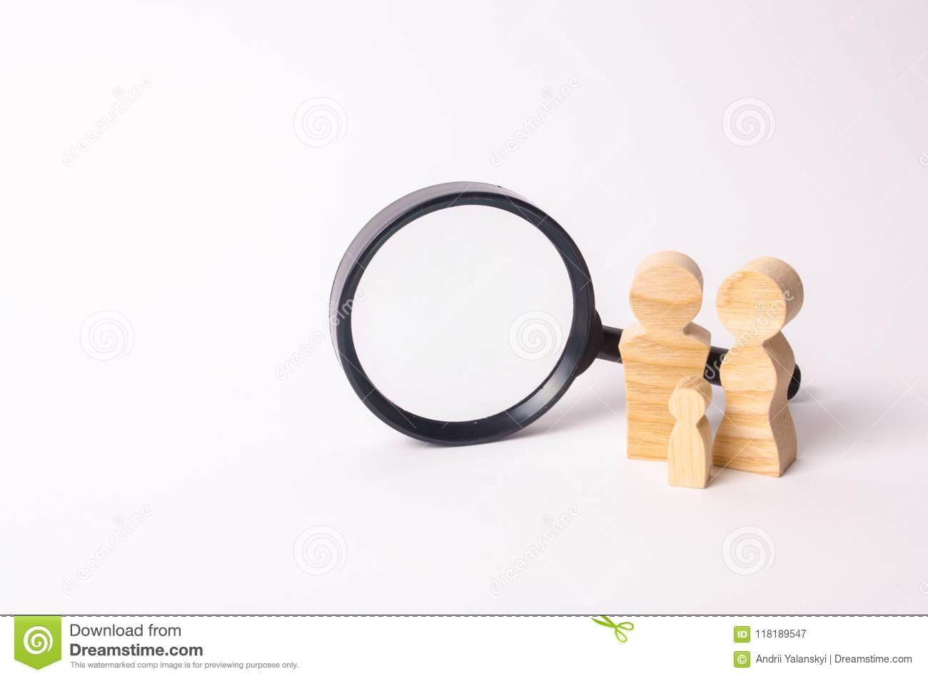 Wooden figures of people stand near the magnifying glass. The family is looking for something. The concept of housing search.
