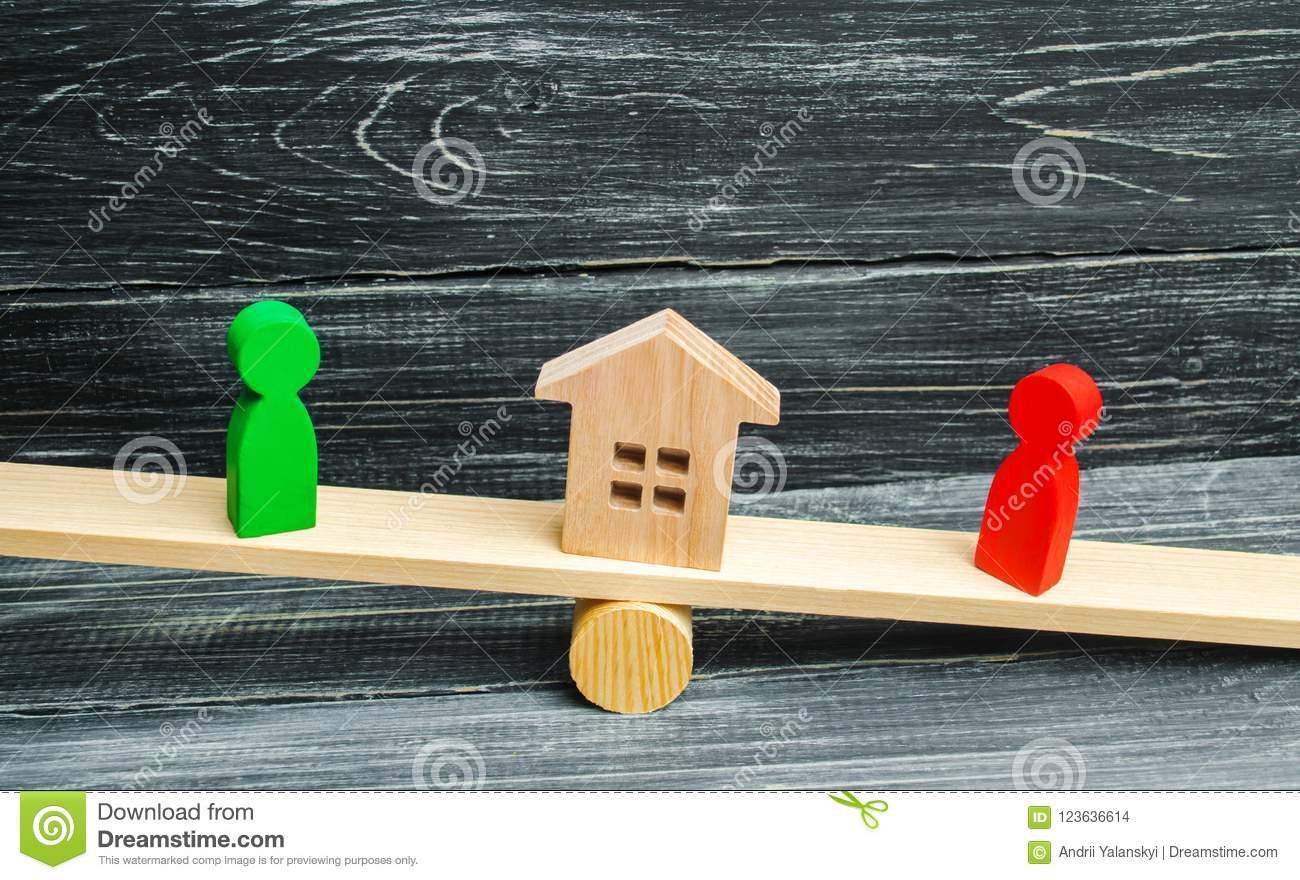 Wooden figures on the scales. clarification of ownership of the house, real estate. court. rivals in business. competition. victor
