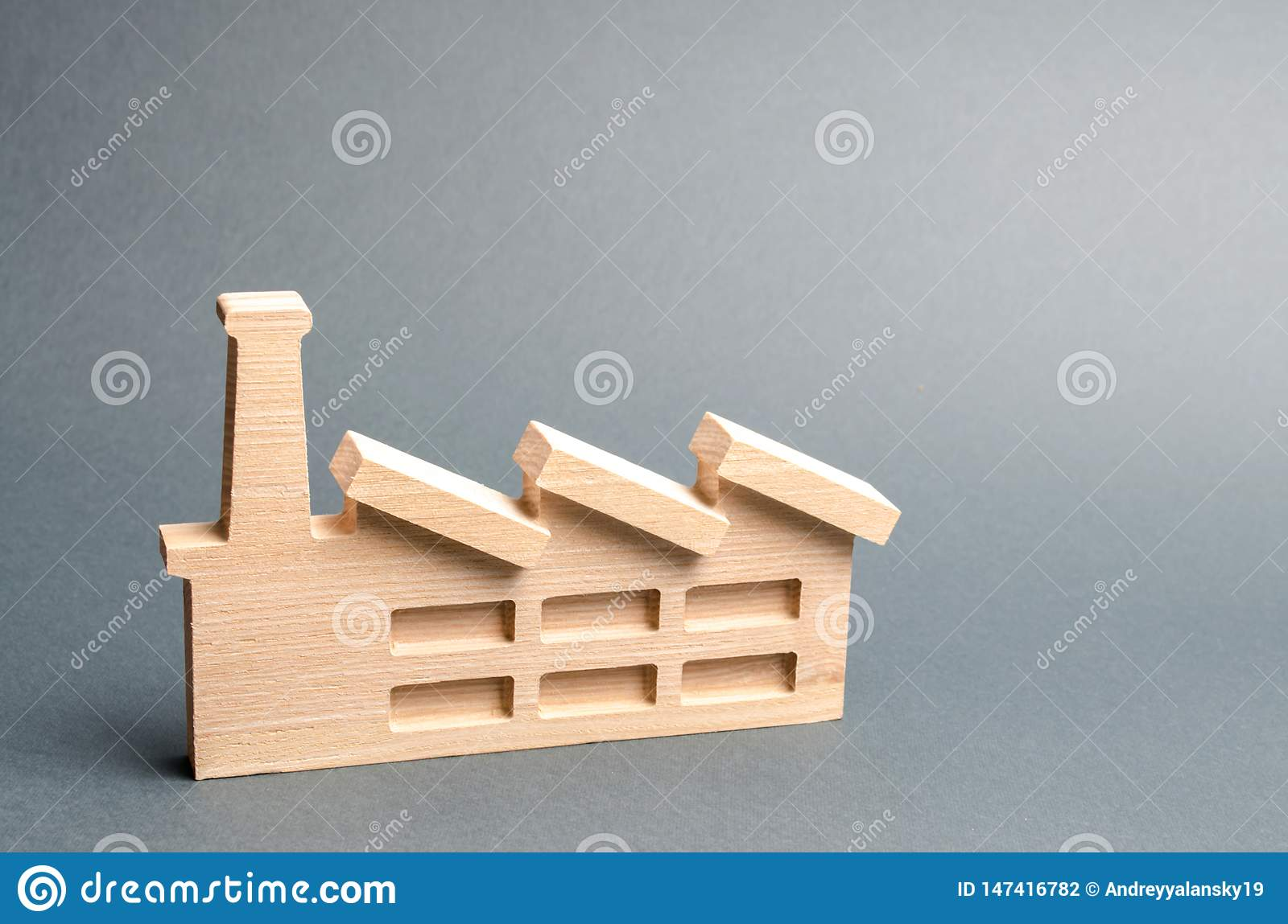Wooden figurine of a plant or factory on a gray background. Recycling raw materials. The concept of industry and production