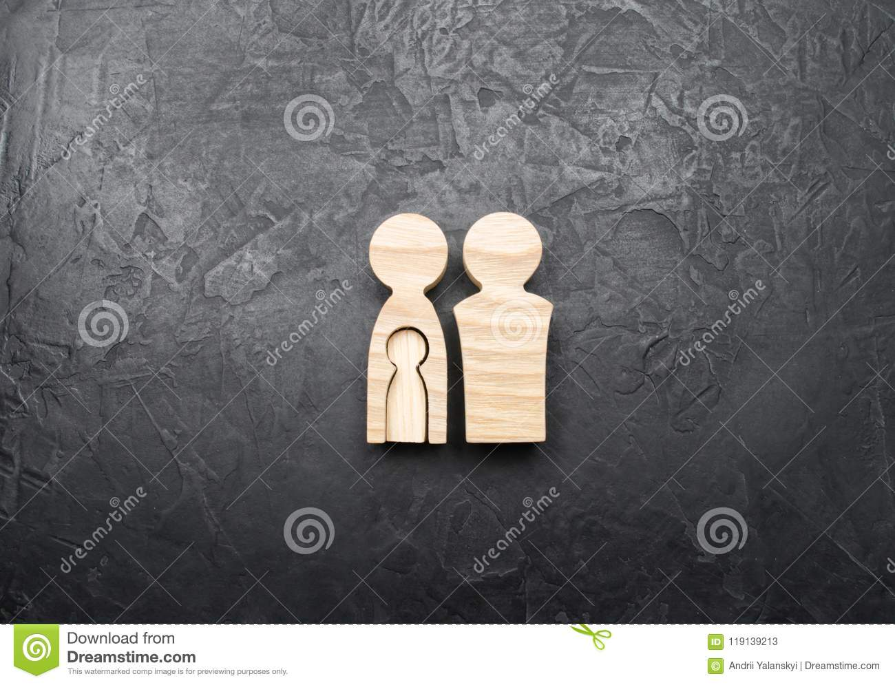 Wooden Figurines Of Parents With The Shape Of A Child Inside The