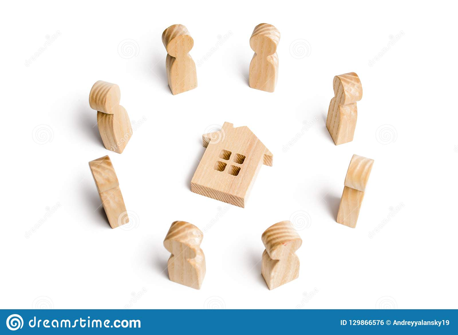 Wooden figurines of people stand around the house. Search for a new home and real estate. Buying or selling a home.
