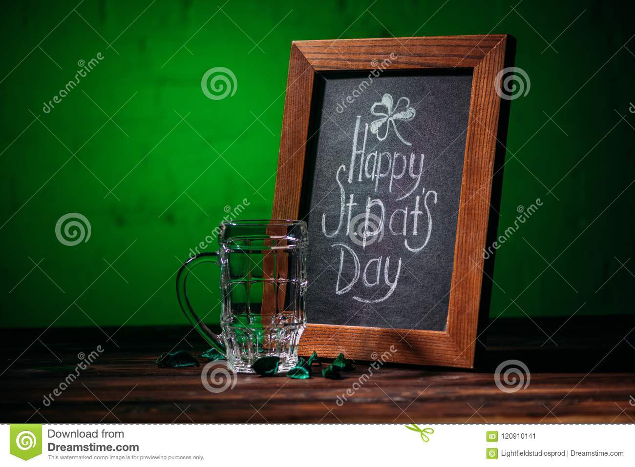 wooden frame with happy st patricks day inscription and empty beer glass