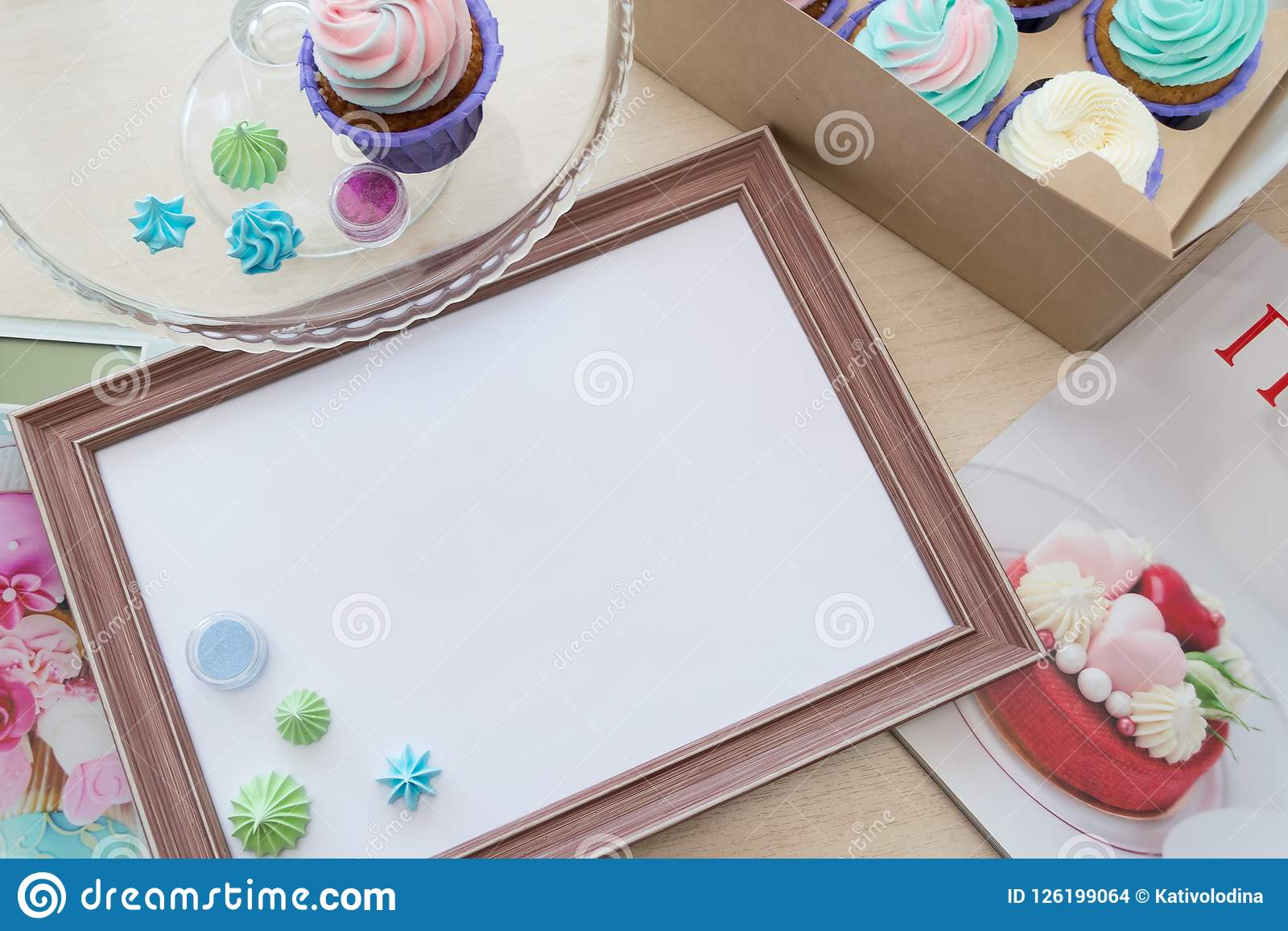 Wooden Frame With White Sheet Around Meringue And Cupcake With Multi ...