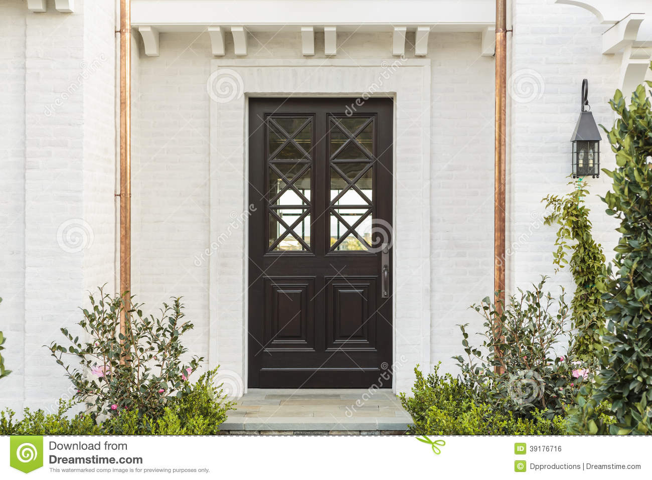 Wooden front door of white brick home with plants stock for White wooden front doors
