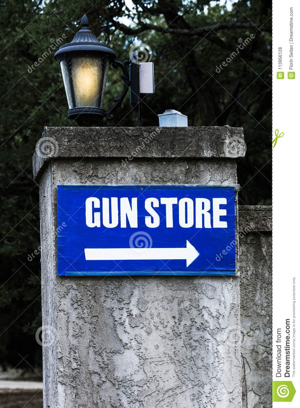 Wooden Gun Store Sign Posted On A Stone Wall With Light Post Stock