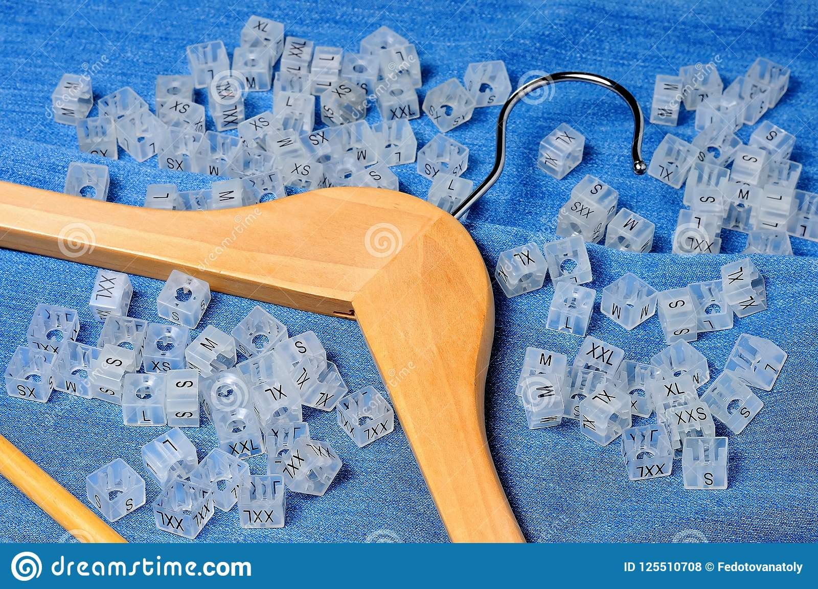 wooden hanger and various plastic clothing size tags stock photo