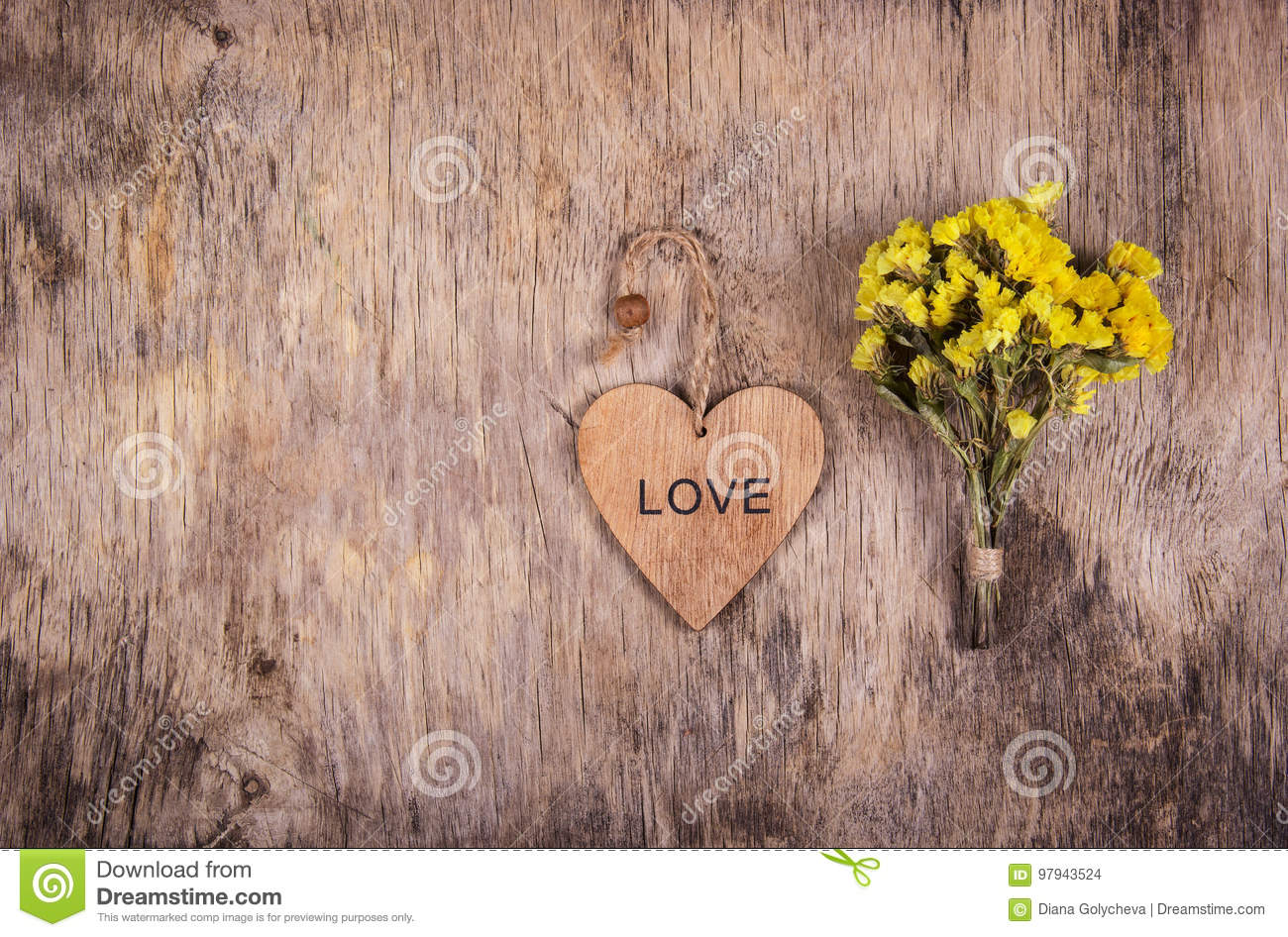 Wooden heart and yellow flowers on an old worn wooden background. Backgrounds and textures. Copy space