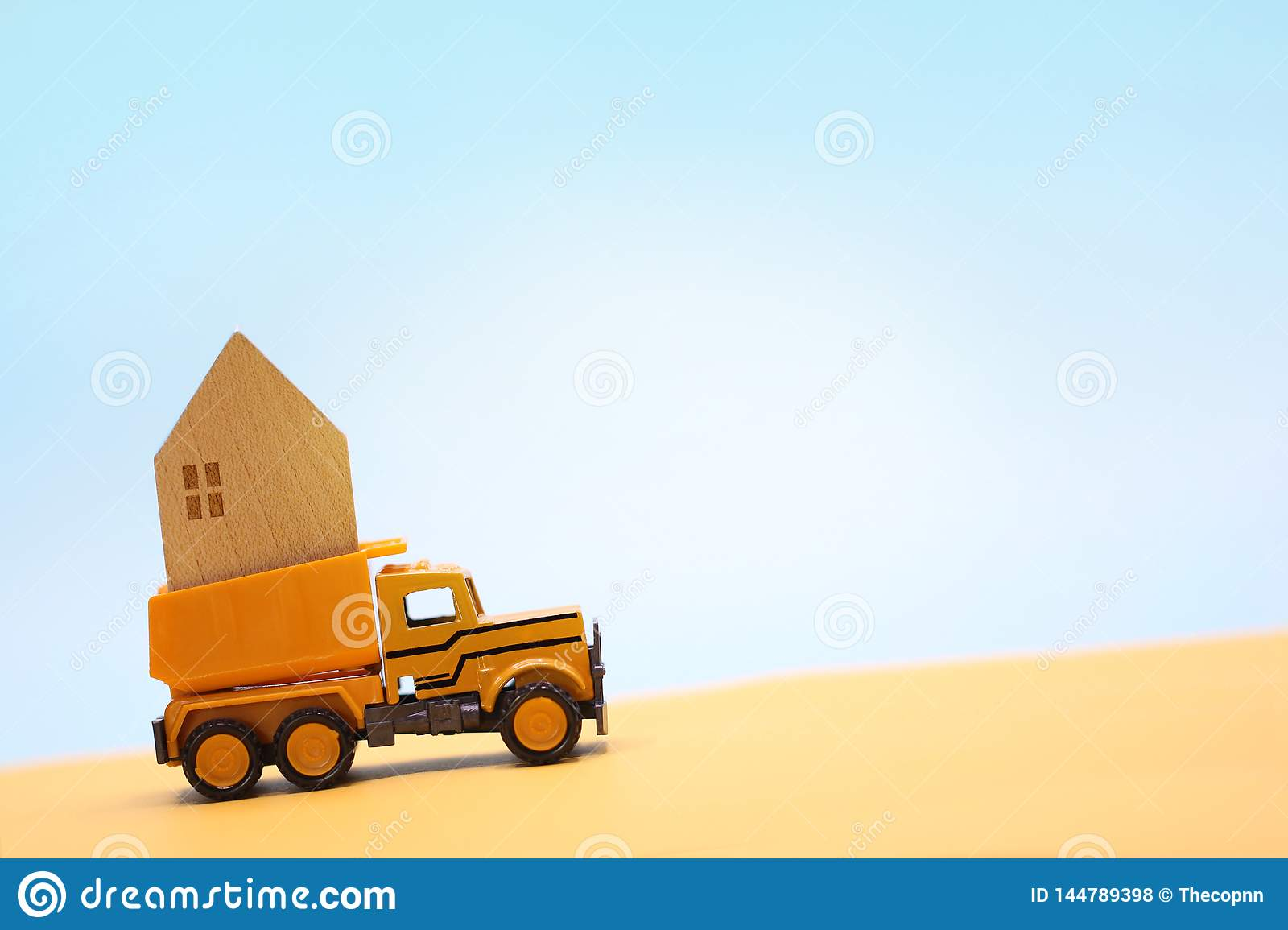 Wooden house carry on yellow toy truck in desert under blue sky