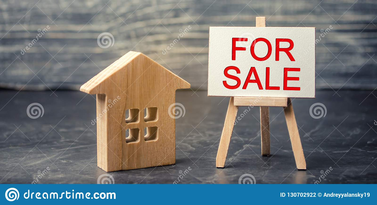 Wooden house and dollars with the inscription `for sale`. sale of property, home. affordable housing. sale of apartments. real est