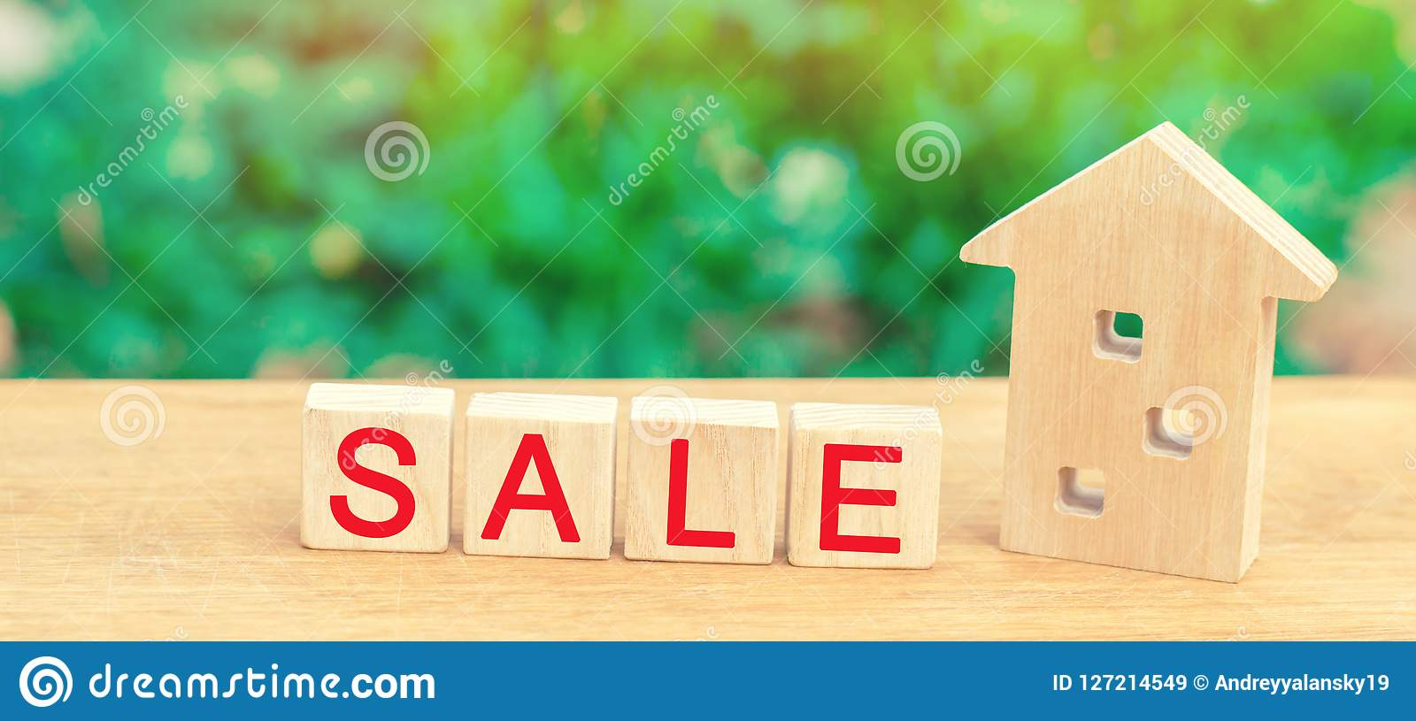 Wooden house with the inscription `sale`. sale of property, home, real estate. affordable housing.