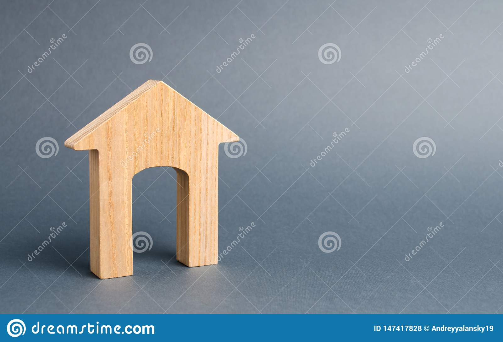 Wooden house with a large doorway on a gray background. Minimalism. Entry, exit, real estate and urbanism. Buying or selling