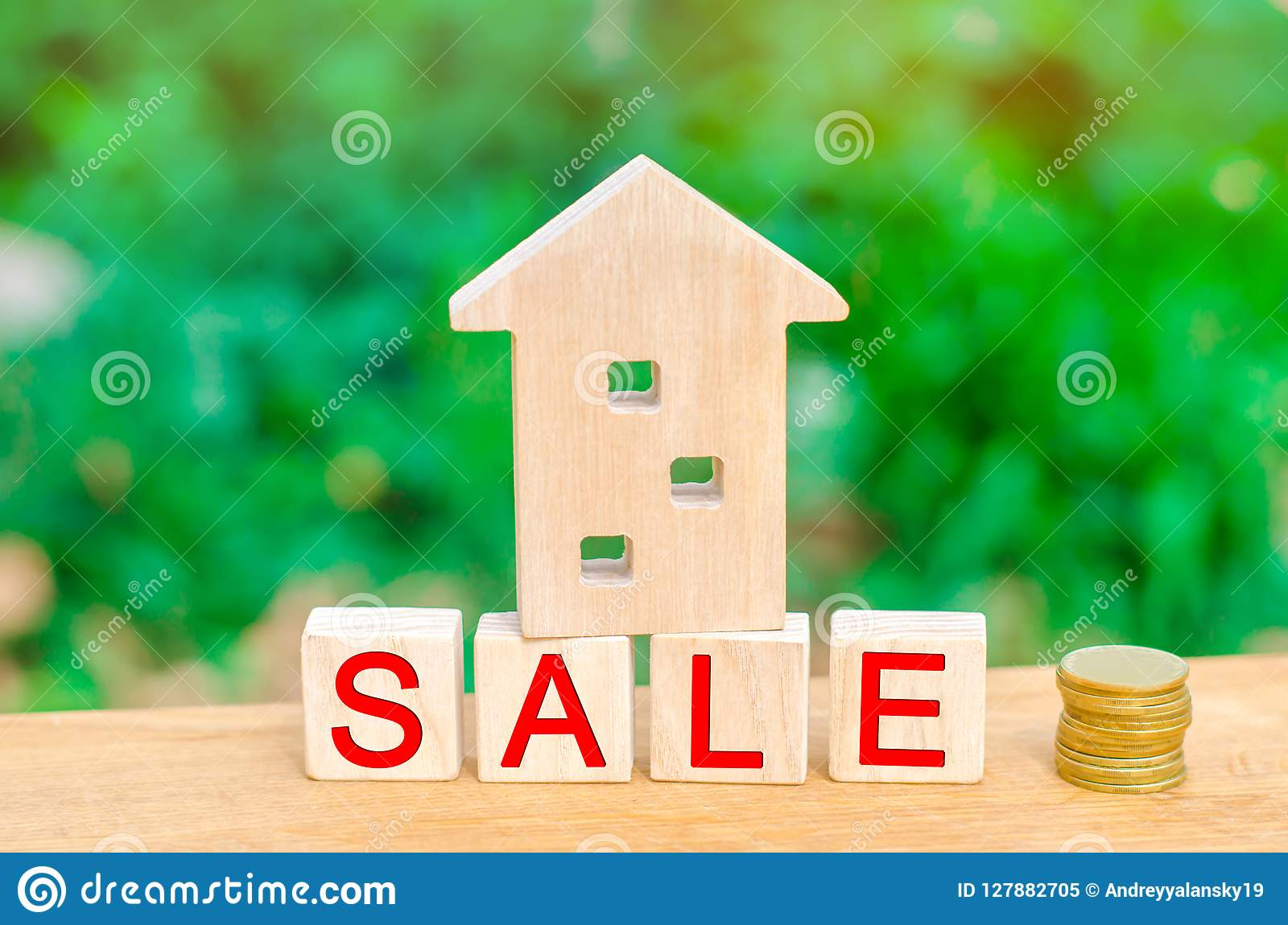 Wooden house and stack of coins with the inscription `sale`. sale of property, home, real estate. affordable housing.
