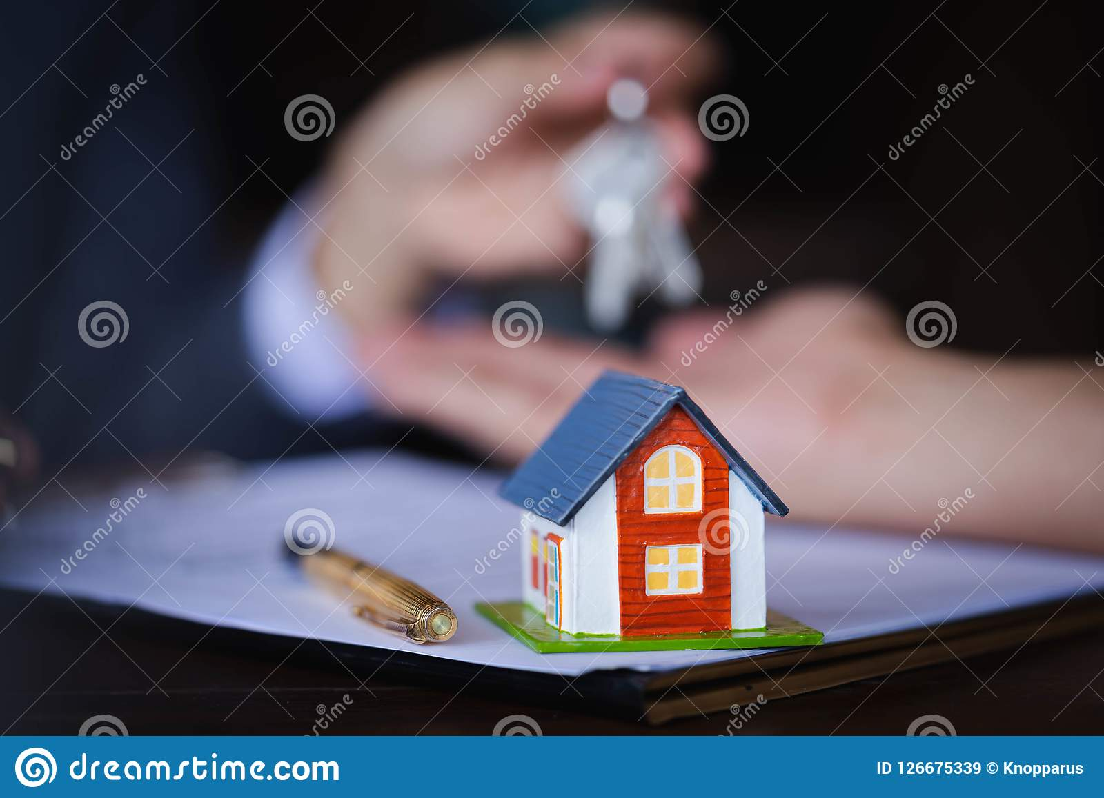 Wooden house on the table background with Real-estate agent giving keys to new property owners after signing contract for realty