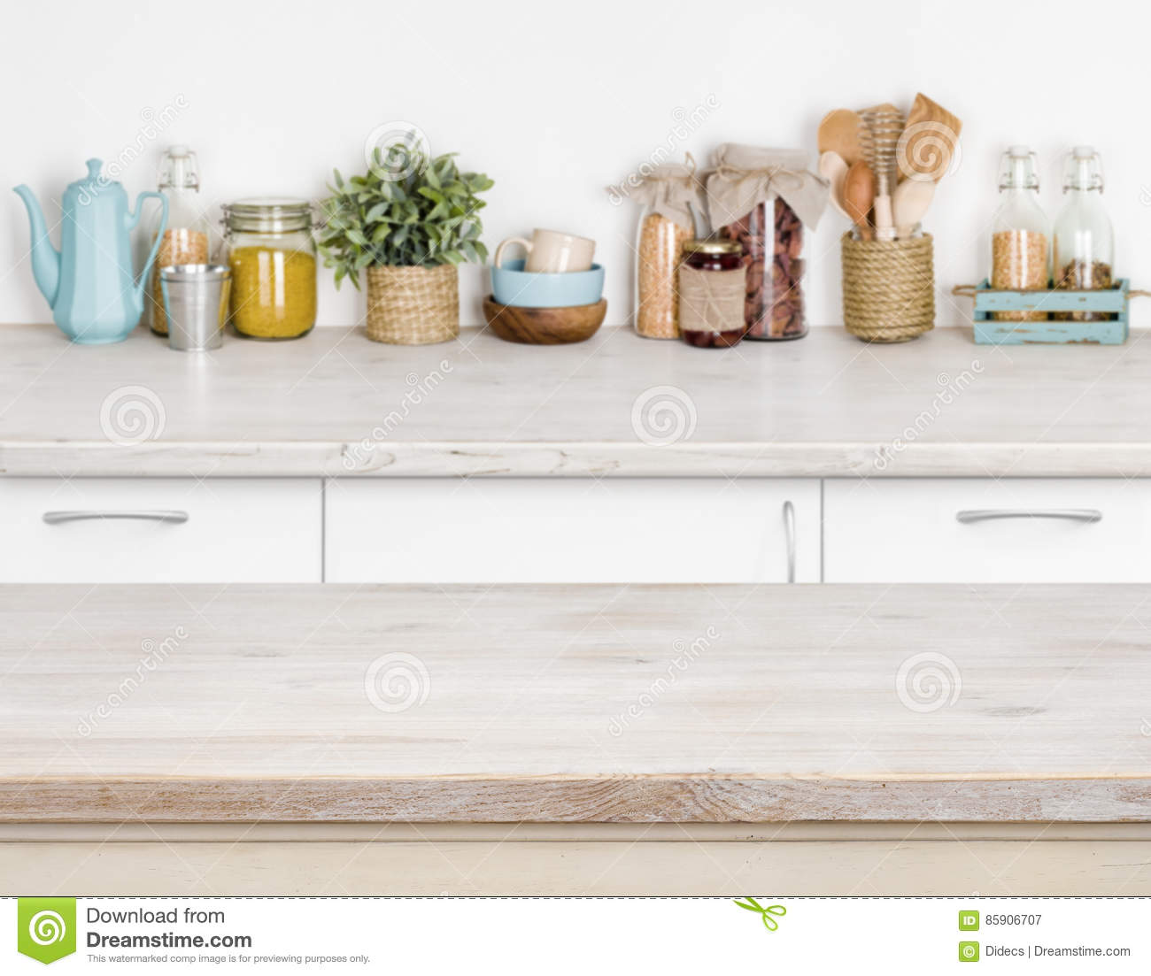 Wooden kitchen table over blurred furniture shelf with food ingredients