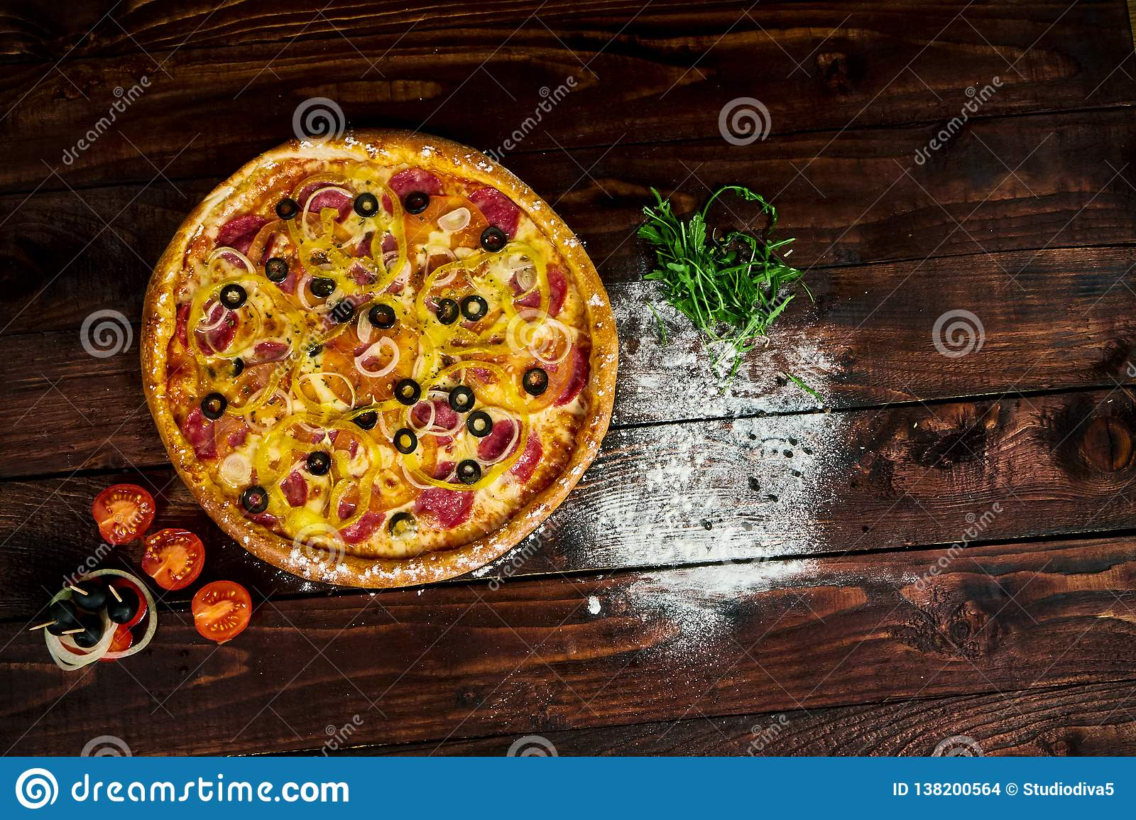 Wooden kitchen table with pizza sprinkled with flour
