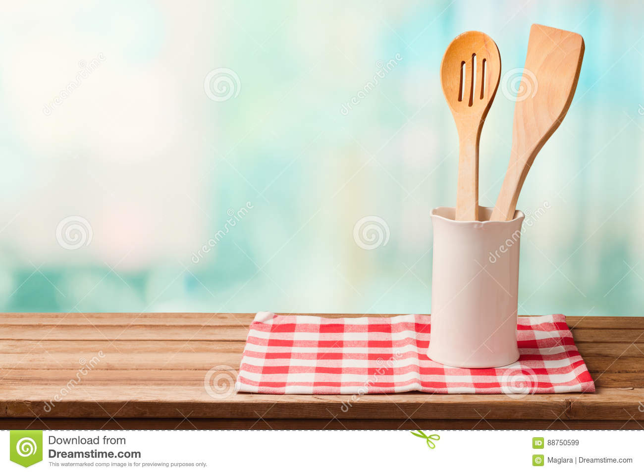 Wooden kitchen utensils on table with tablecloth over blue