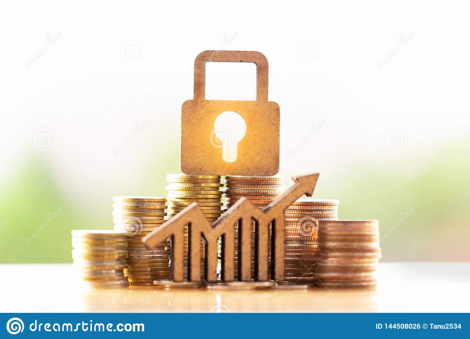 Wooden lock and stack of coins in concept of savings and money growing or energy save.