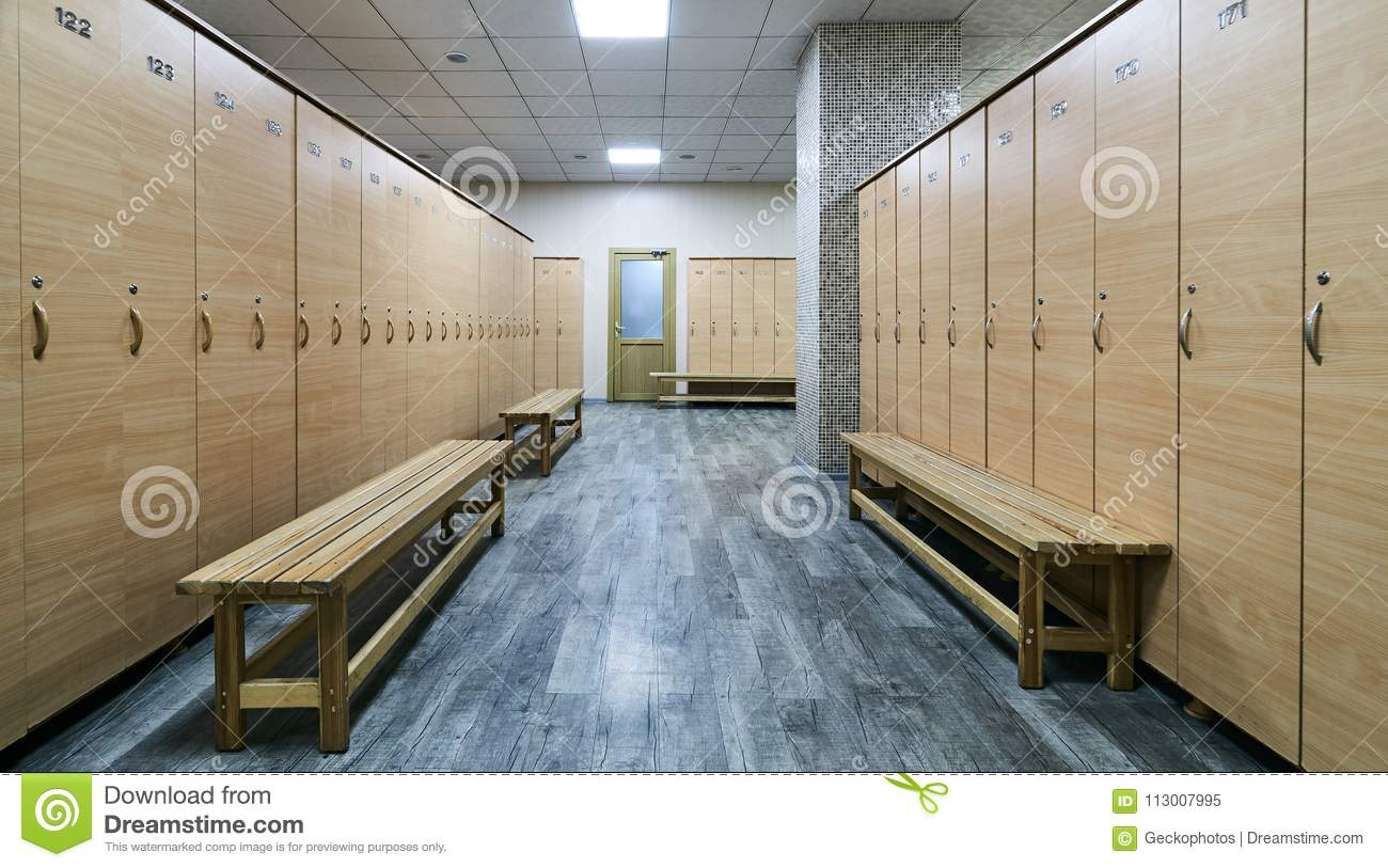 Wooden lockers with a wood bench in a locker room stock image