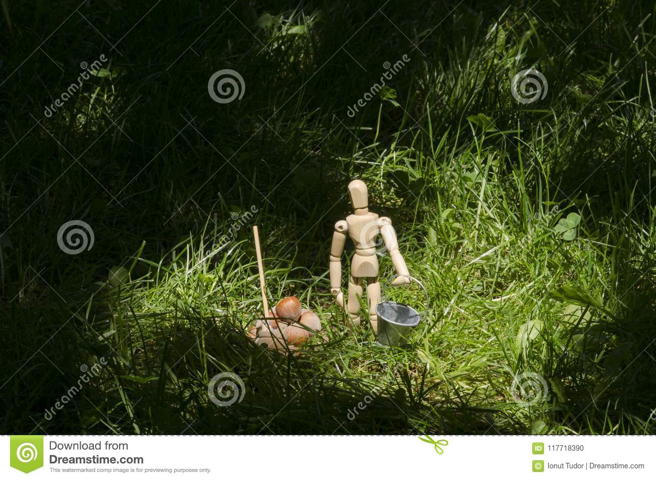 Wooden mannequin in green grass with miniature bucket and shovel