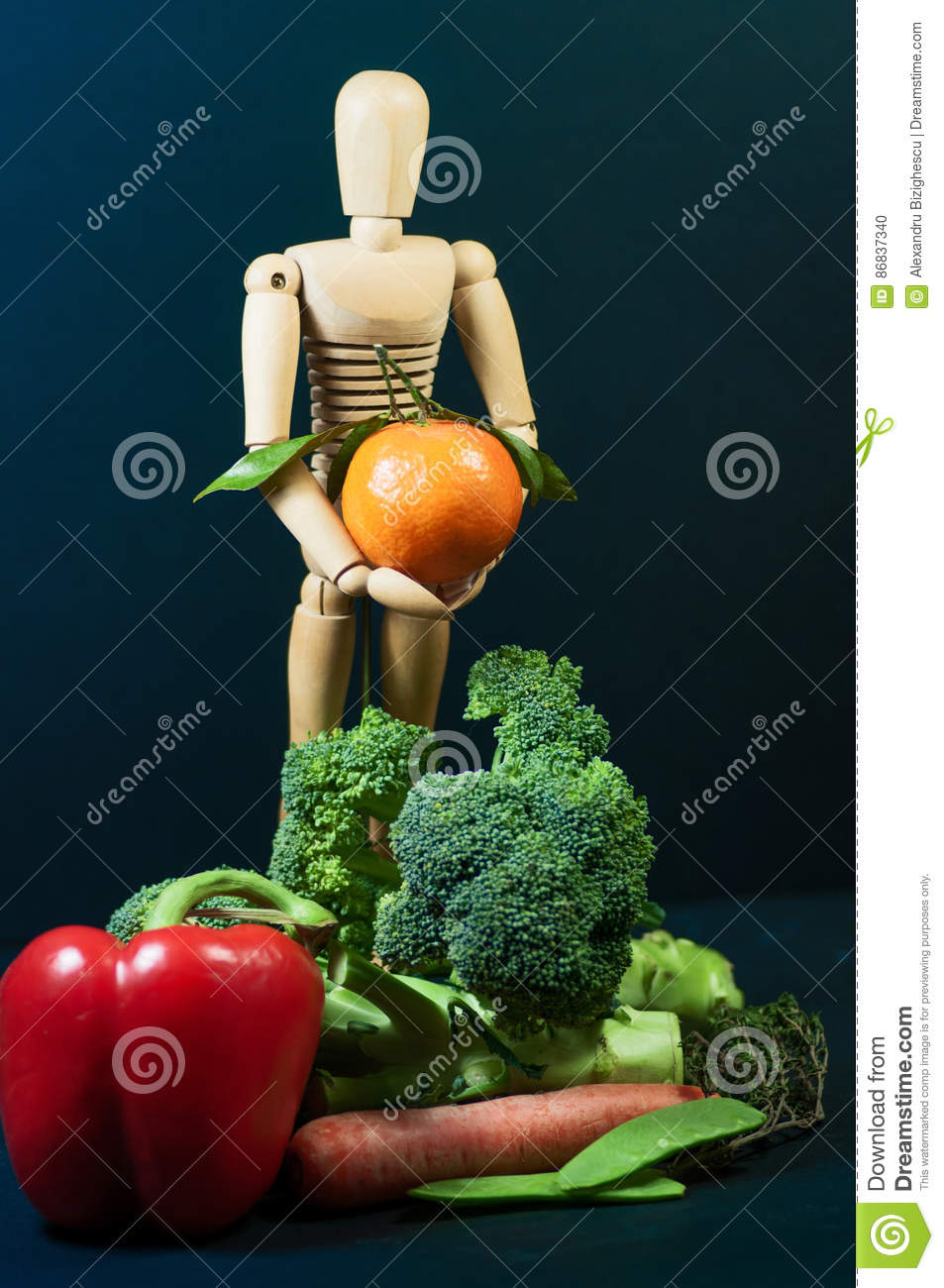 Wooden mannequin and a mix of vegetables and fruits