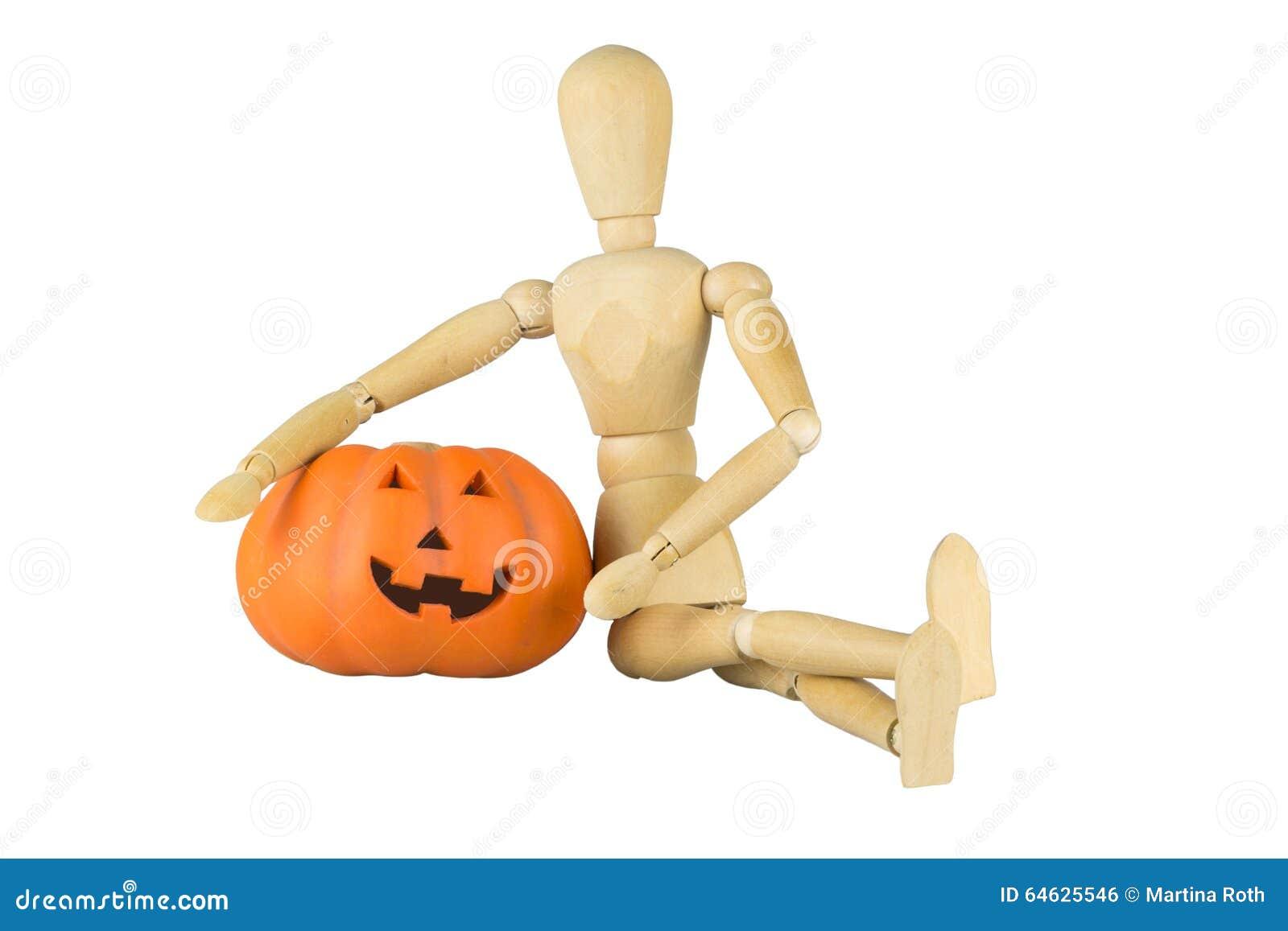 Wooden mannequin posing with a pumpkin