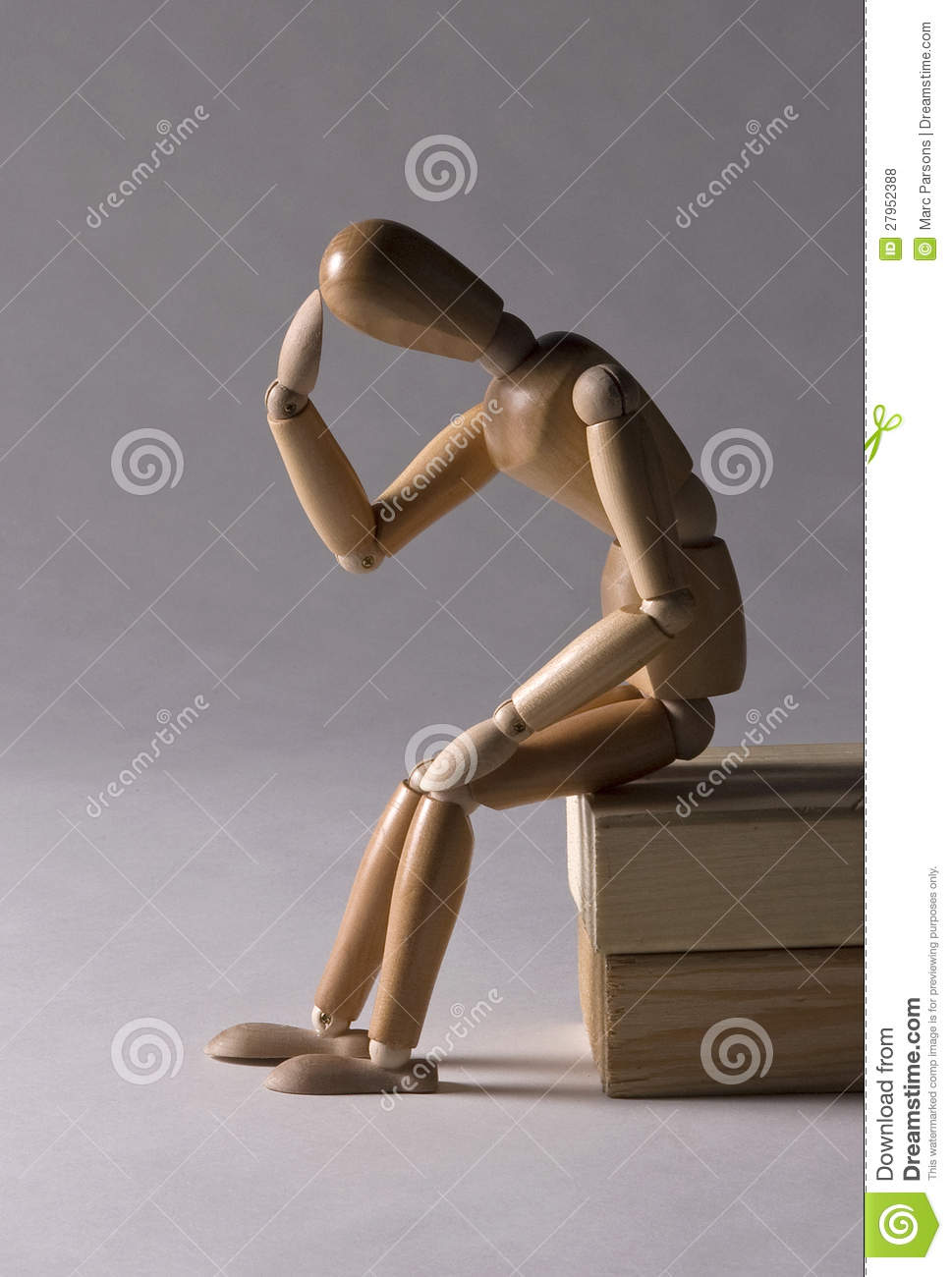 Wooden modeling mannequin sitting on blocks in a thinking pose, clean ...